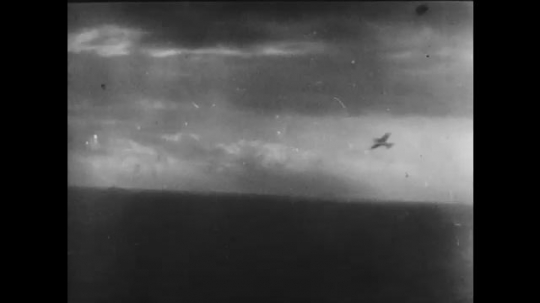 UNITED STATES 1940s: Ship gun fires / Plane hit / Shots over water / Plane going down / Plane in flames / Plane goes down in water, soldiers in foreground.