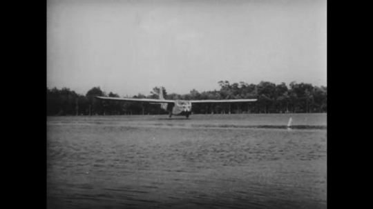 UNITED STATES 1940s: Glider lands on water / Paratroopers stand / Paratroopers jump from plane / Title card.
