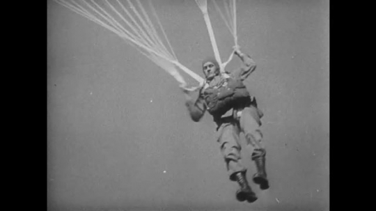 UNITED STATES 1940s: Paratrooper lands, tumbles / Title card / Soldiers in jungle, gun fires / Close up, soldier gives command.