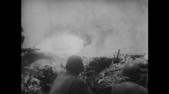 UNITED STATES 1940s: Soldiers with flamethrower, explosion / Tracking shot of dead soldiers.