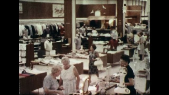 UNITED STATES 1960s: Long shot of department store interior / Cashier rings up customer / Shoppers in grocery store.