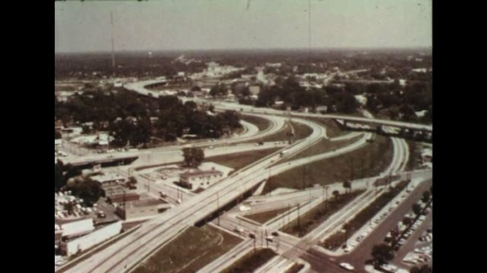 UNITED STATES 1960s: Aerial view of highway system / Pan of truck driving to factory / Train tracks next to factory, train pulls away from camera.