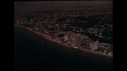 UNITED STATES 1960s: Aerial view of Florida coast / Aerial view of hotel / People around hotel pool.