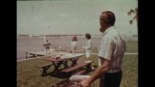 UNITED STATES 1960s: Family having barbecue by lake / Panning shot of large crowd.