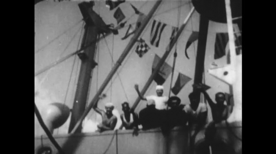 UNITED STATES 1950s: Sailors wave from ship, pan to sign on side of ship / Grain pours from chute / People watch grain pour / Women sort clothes / High angle view, women sort clothes.