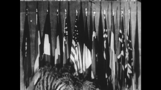 UNITED STATES 1950s: United Nations flags / Officials in front of flags / Soldiers training with firearms.