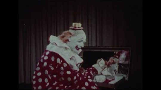 UNITED STATES 1950s : A clown narrates while putting makeup on his face.