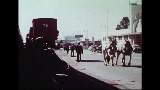UNITED STATES 1950s : Two horses pull a red wagon down a ramp on a city street.