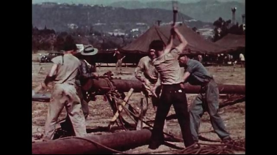 UNITED STATES 1950s : Four men take turns hammering a stake into the ground.