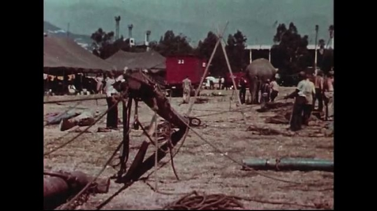 UNITED STATES 1950s : The first center pole of a circus tent, the king pole, is put up and held in place by ropes.