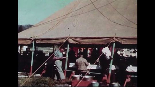 UNITED STATES 1950s : Men and women sitting around inside a tent as they eat their breakfast.