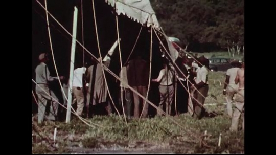 UNITED STATES 1950s : Many men work together to bring up the side pole of a circus tent.