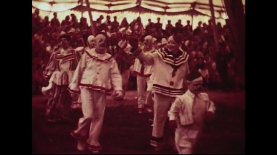 UNITED STATES 1950s : Clowns walk into a circus show as the crowd cheers.