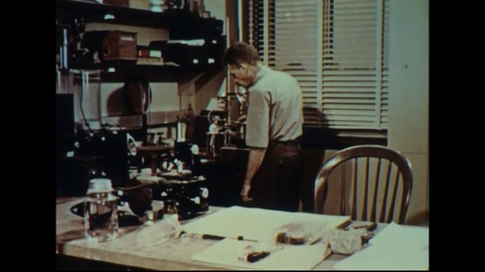 UNITED STATES 1950s: Scientist in lab talks into camera, picks up crystal / Close up of crystal in hands / Hands with crystal, grab smaller crystal / Close up of small crystal.