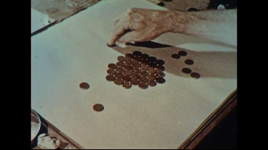 UNITED STATES 1950s: View of pennies on table / Close up of ball bearings.