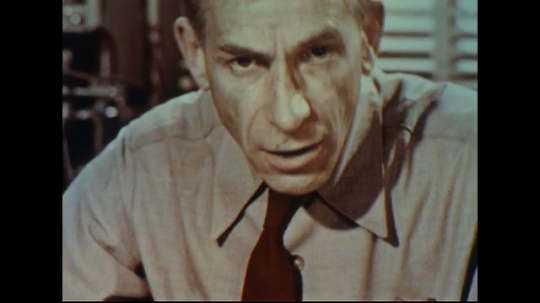 UNITED STATES 1950s: Close up, scientist speaks into camera / Hands cut crystal with razor.