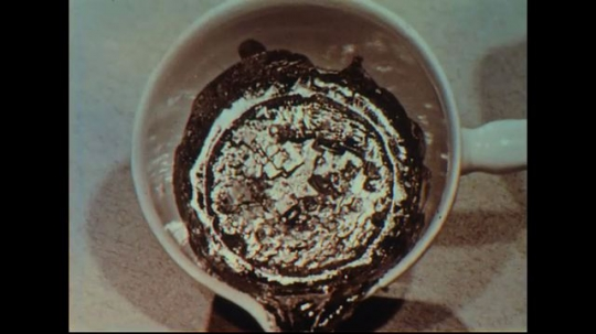 UNITED STATES 1950s: Close up, crystals in liquid in bottom of cup / Hands hold piece of metal with crystals.