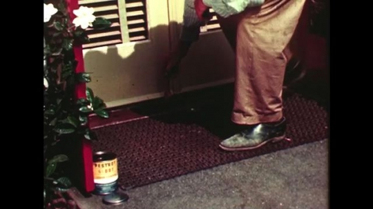 UNITED STATES 1940s: Man paints pesticide under patio door / Close up of hand painting.