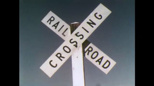 UNITED STATES: 1970s: railway crossing sign. Car approaches junction. Railway tracks. Bus crosses tracks