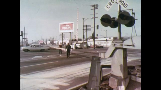 UNITED STATES: 1970s: workmen repair crossing gates. Car drives across tracks. Model from above