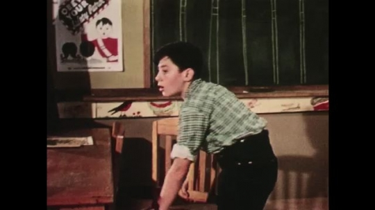 UNITED STATES: 1950s: boy moves chair in classroom. Boy holds paper.