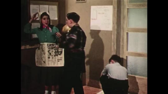 UNITED STATES: 1950s: girl wears newspaper clothes in classroom play. Teacher talks to camera. Man sits at desk