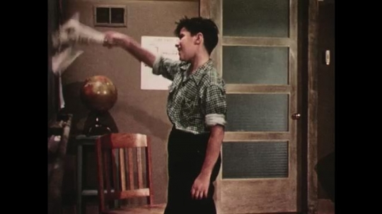 UNITED STATES: 1950s: boy talks and waves paper in classroom drama. Boy enters class.
