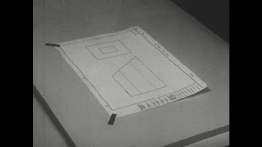 UNITED STATES: 1960s: hands put tracing paper over illustration. Hands stick tape around paper.