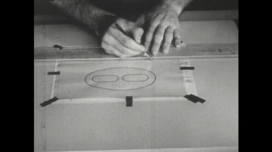UNITED STATES: 1960s: finger points at paper drawing. Hands use cloth to clean drawing tools.