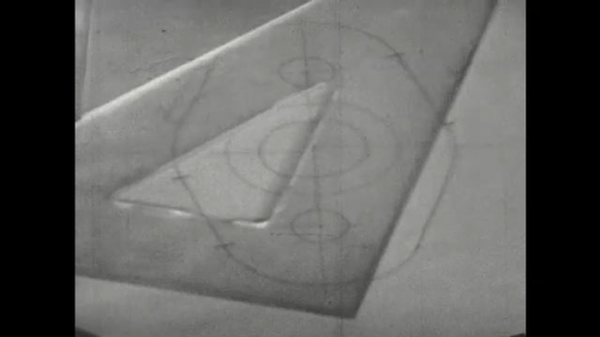 UNITED STATES: 1960s: hand moves plastic triangle over drawing. Fingers draw marks on illustration