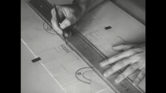 UNITED STATES: 1960s: hand draws lines on paper with ruler.