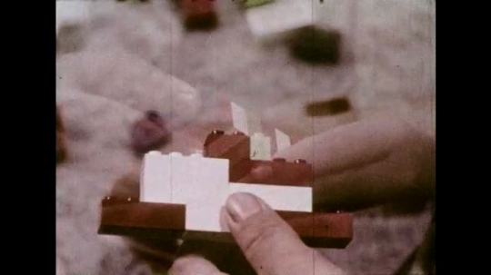 UNITED STATES 1970s: Dissolve to close up, hands stack Lego pieces / Dissolve to high angle view, child playing with Legos / Dissolve to close up, hands connect Lego pieces.
