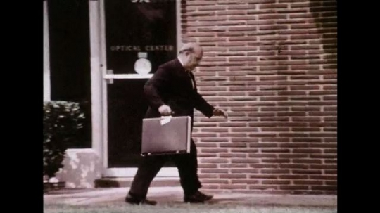 UNITED STATES 1970s: Panning shot, man skips on sidewalk / Men carry board across sidewalk, man runs into board / Man falls / Zoom in on man's face, man looks into camera, images freezes.
