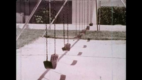 UNITED STATES 1970s: Boy sits on swing, starts to spin, zoom in on boy / View of scenery spinning / Boy on swing / Scenery spinning.