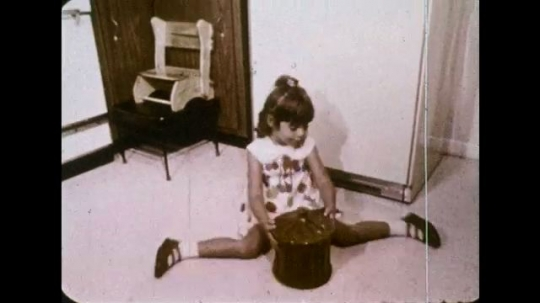 UNITED STATES 1970s: Fast reverse of girl getting cookie jar / Girl takes jar from cupboard / Feet slip off counter / Jar flies in air / Jar smashes on floor.