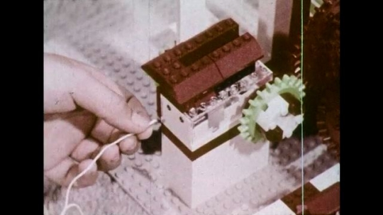 UNITED STATES 1970s: Child's hand plugs wire into Lego battery box / Girl looks at Lego structure, hand touches structure.