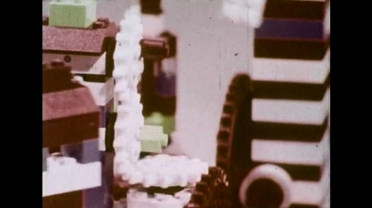 UNITED STATES 1970s: Close up of Lego pieces moving / Boy and girl with Lego structure / Girl