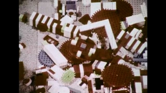 UNITED STATES 1970s: High angle view of broken Lego pieces, zoom out to show boy and girl / Boy walks down dark alley / Player catches football.