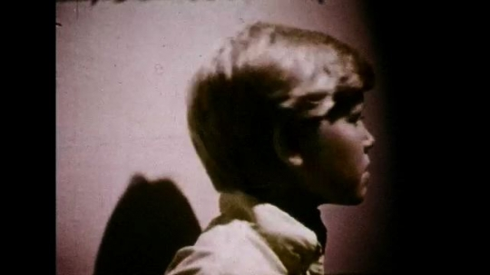UNITED STATES 1970s: Boy in dark alley / Moving camera, view of alley / Slow motion images of pills, drugs / Boy walks, turns corner / Boy looks around corner, image freezes.