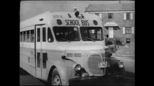 UNITED STATES- CIRCA 1950: School bus drives down suburban street, young children sit in seats. Atomic flash prompts them to duck behind seats.