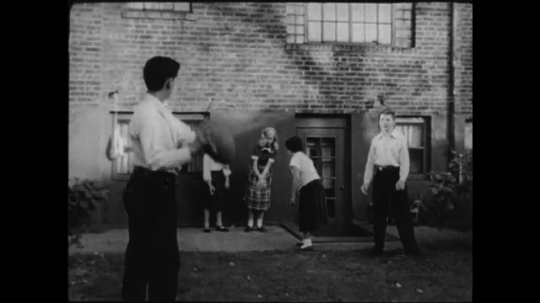 UNITED STATES- CIRCA 1950: Children play in backyard. All respond when hearing siren by dropping toys and returning inside.