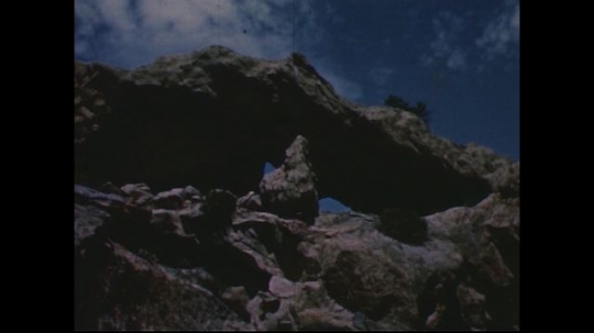 UNITED STATES 1950s: Low angle view of rock formation / Pan across rock formation / Men in front of cave with net / Men climb into cave.