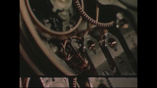 UNITED STATES 1950s: Close up of moving clockworks / Clock face.