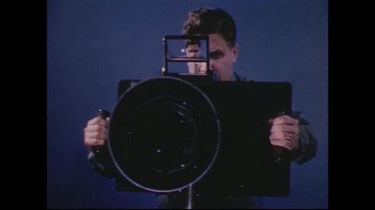 UNITED STATES 1950s: Man tilts large aerial camera / Close up of camera lens / Close up of human eye.