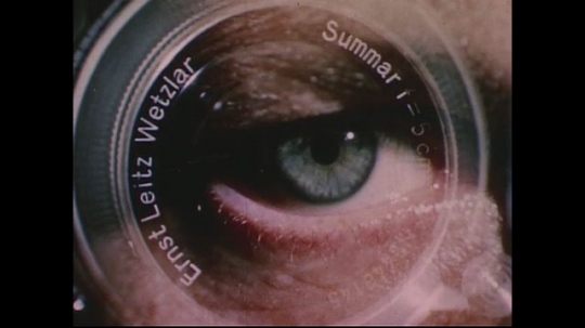 UNITED STATES 1950s: Camera lens superimposed over human eye / Eye chart, man's head in foreground / Zoom in on eye chart, letters go in and out of focus.