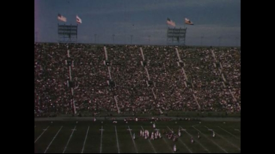 UNITED STATES 1950s: Long shot of football stadium / Football players on field / Spectators cheer in stands / Hands playing piano superimposed over model of ear / Zoom in on hands playing piano.
