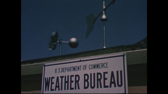 UNITED STATES 1950s: Sign for weather bureau, weather vanes on roof  / Weather tracking equipment positioned / Equipment from behind / Close up of gauges / Weather balloon released.