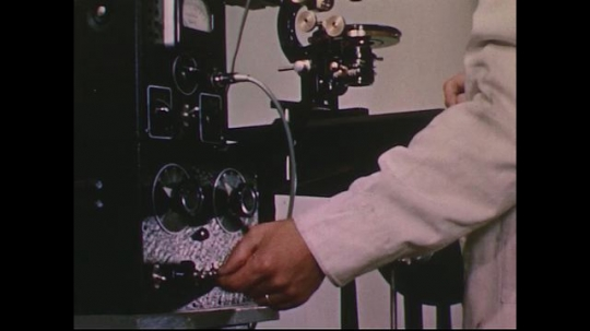 UNITED STATES 1950s: Scientist turns on equipment / Slide under microscope / Magnified fish embryo.