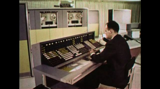 UNITED STATES 1960s: A man sits at a desk observing data movement.