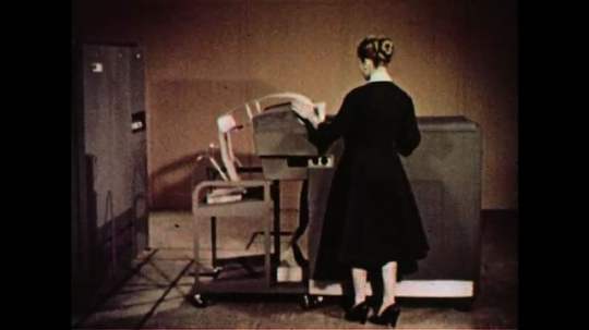 UNITED STATES 1960s: A woman stands by a printer as it prints on spools of paper.